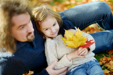 Young father and his daughter have fun at autumn