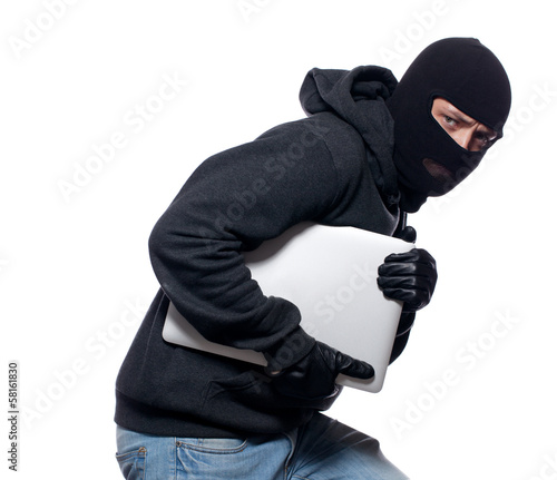 Thief stealing a laptop computer - 58161830