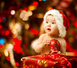 Christmas baby in santa hat near red present gift box