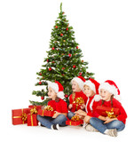 Christmas kids in Santa hat  with presents sitting under fir tre