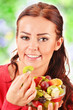 Young woman eating fruit salad