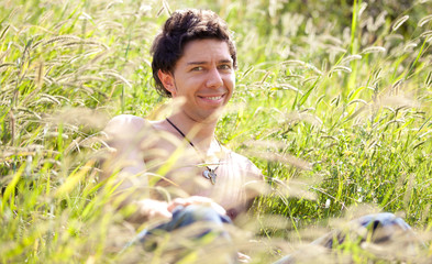 Closeup portrait of handsome smiling man lying in high grass