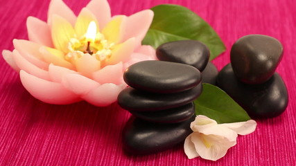 A pile of black spa therapy stones with lotus candle