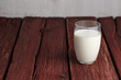 Glass of milk standing on old wooden table