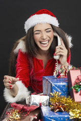 Laughing radiant woman taking a funny phone call on Christmas