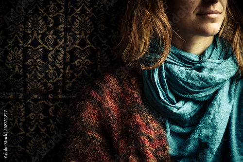 Young woman with scarf sitting on vintage sofa