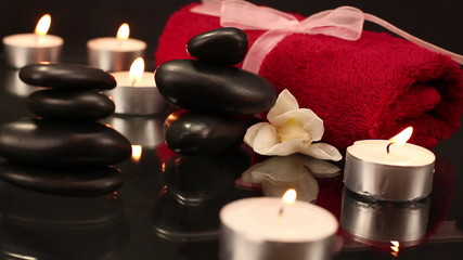 A pile of black spa therapy stones and candles