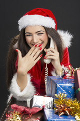 Young lady in Santa costume laughing while talking on telephone