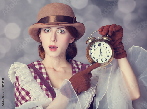 Beautiful redhead women with clock.