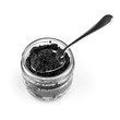 Black caviar in a glass jar with teaspoon isolated