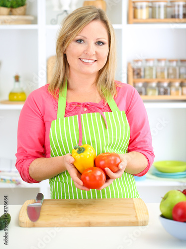Happy smiling woman in kitchen  holding fresh vegetables in her