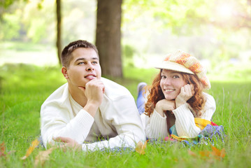 Young beautiful couple on green grass in autumn