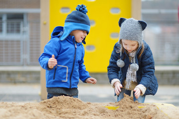 Two kids playing in a sandbox
