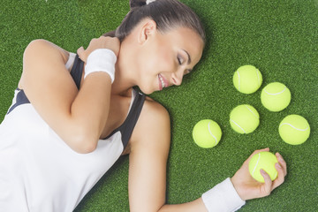Portrait of Dreaming Female Tennis Player Lying on Artificial Gr
