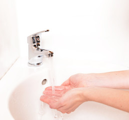 Close-up of human hands being washed under faucet in bathroom