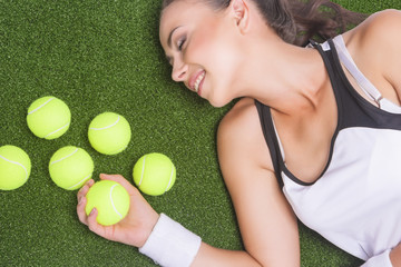 Happy Smiling Tanned Female Sportswoman Lying on Artificial Gras