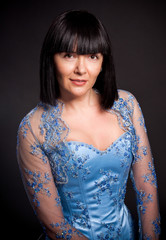 portrait of brunette lady with short haircut and in blue corset