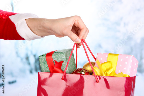 Hand holds package with New Year balls and gifts