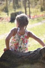 Mädchen mit Zöpfen auf einem Baumstamm