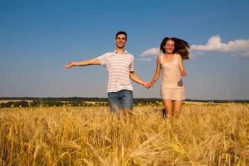 Young couple runningthrough  wheat field
