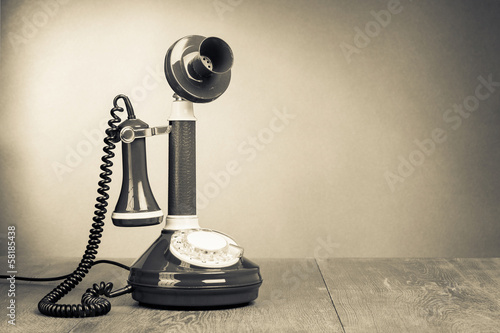 Retro rotary telephone on table for vintage background