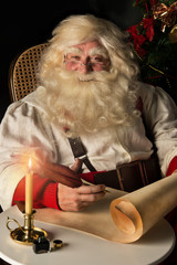 Santa Claus sitting at home and writing on old paper roll to do