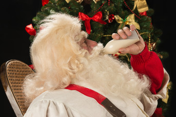 Happy Santa Claus drinking milk from glass bottle against Christ