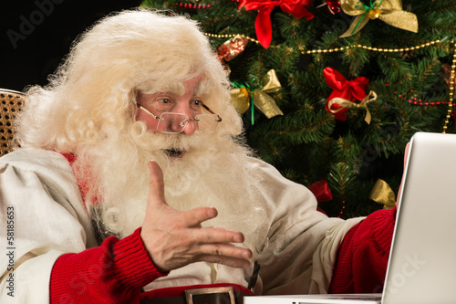 Santa Claus using laptop at home against Christmas Tree and is r