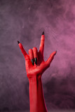 Heavy metal, red devil hand with black nails