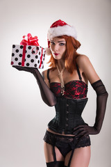 Pretty girl wearing pinup outfit and Santa Claus hat, holding gi