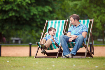 Happy father and son having rest in city park on summer day