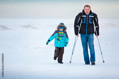 Man with crutches together with son walking along winter beach