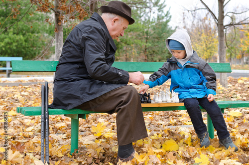Disabled senior man teaching his grandson to play chess
