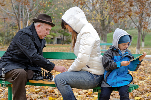 Boy sitting his mother and grandfather play tablet computer