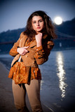brunette girl posing at evening against moonlight and sea