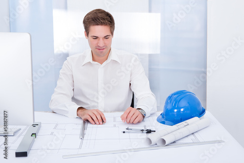 Young Architect Drawing Plan On Blueprint