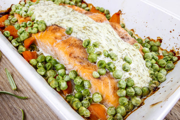 Roasted salmon with dill sauce and green peas.