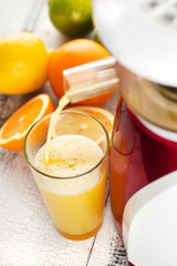 Slow juicer and orange juice.
