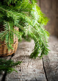 Green Branches of Fir in a Basket on wooden table