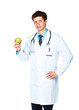 Portrait of a male doctor holding green apple on white