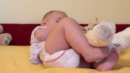 Hyperactive baby playing with teddy bear on the bed