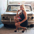 Sensual blonde woman standing near abandoned car.