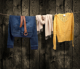 Women's clothing on a clothesline on wood background