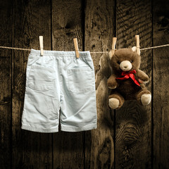 Baby clothes and a teddy bear on clothesline
