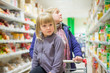 Mother with daughter in shopping cart select products on shelves