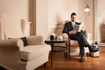 Young businessman relaxing reading a book sit on armchair.