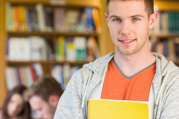 Male student with others in background at the library