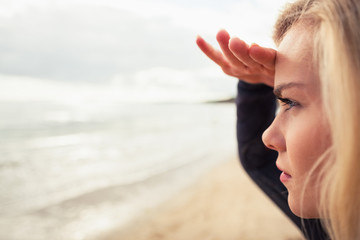 Side view of a beautiful blond shielding eyes at beach