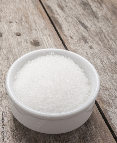 sugar in white bowlon wooden background