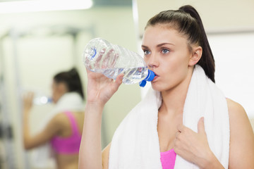 Close up of a woman drinking water in gym